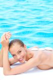 Mujer sonriente que toma el tratamiento del balneario al lado de piscina Imagenes de archivo