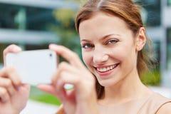 Mujer sonriente que toma imágenes con smartphone Imagenes de archivo