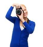 Mujer sonriente que toma la imagen con la cámara digital Fotografía de archivo libre de regalías