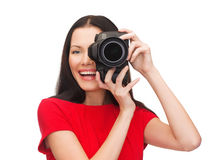 Mujer sonriente que toma la imagen con la cámara digital Imagen de archivo libre de regalías