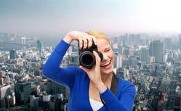 Mujer sonriente que toma la imagen con la cámara digital Foto de archivo libre de regalías