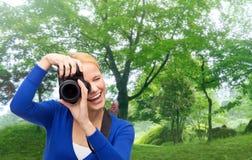 Mujer sonriente que toma la imagen con la cámara digital Fotos de archivo