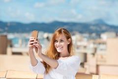 Mujer sonriente que toma su fotografía Imagen de archivo libre de regalías