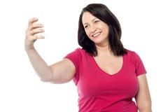 Mujer sonriente que toma un selfie imagenes de archivo