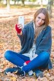 Mujer sonriente que toma un selfie en un parque del otoño Imagen de archivo libre de regalías
