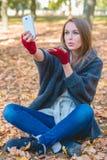 Mujer sonriente que toma un selfie en un parque del otoño Fotografía de archivo libre de regalías