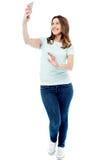Mujer sonriente que toma una foto con el teléfono móvil Fotos de archivo