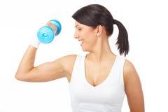 Mujer sonriente que trabaja con pesas de gimnasia Imagen de archivo