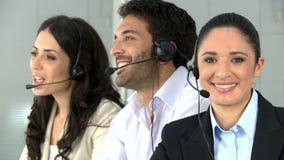 Mujer sonriente que trabaja en el centro de atención telefónica metrajes
