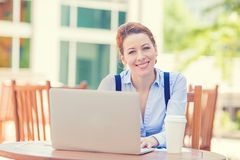 Mujer sonriente que trabaja en el ordenador portátil fuera del café de consumición de la oficina corporativa Imagen de archivo libre de regalías