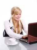 Mujer sonriente que trabaja en la computadora portátil en oficina Fotos de archivo