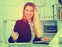 Mujer sonriente que trabaja en la oficina Imágenes de archivo libres de regalías