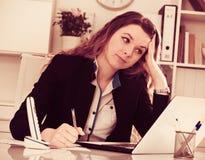 Mujer sonriente que trabaja en la oficina Fotos de archivo