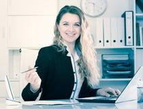 Mujer sonriente que trabaja en la oficina Fotografía de archivo