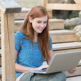 Mujer sonriente que trabaja en un ordenador portátil Imágenes de archivo libres de regalías