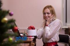 Mujer sonriente que trabaja en una oficina en la Navidad Fotos de archivo libres de regalías