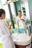 Mujer sonriente que usa el cuarto de baño de la loción del cuidado de piel foto de archivo libre de regalías