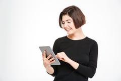 Mujer sonriente que usa el ordenador de la tableta Imágenes de archivo libres de regalías