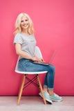 Mujer sonriente que usa el ordenador portátil en la silla Fotografía de archivo libre de regalías