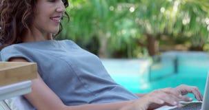 Mujer sonriente que usa el ordenador portátil en silla de cubierta metrajes