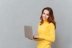 Mujer sonriente que usa el ordenador portátil y la mirada de la cámara Imagenes de archivo