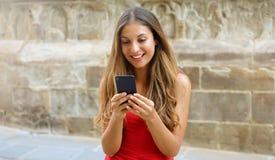 Mujer sonriente que usa el teléfono móvil app para jugar a los videojuegos en línea Mujer de la ciudad que se relaja Forma de vid imagen de archivo libre de regalías