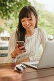 Mujer sonriente que usa el teléfono móvil en la cafetería Imagen de archivo