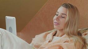 Mujer sonriente que usa la tableta digital mientras que miente en cama de hospital metrajes