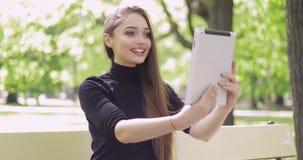 Mujer sonriente que usa la tableta en parque almacen de metraje de vídeo