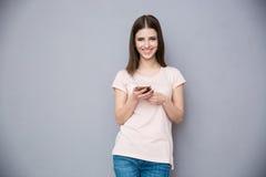 Mujer sonriente que usa smartphone Foto de archivo