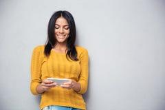 Mujer sonriente que usa smartphone Imagen de archivo