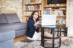 Mujer sonriente que usa un ordenador portátil en casa imagen de archivo libre de regalías