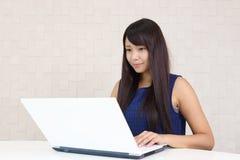 Mujer sonriente que usa una computadora port?til fotografía de archivo libre de regalías