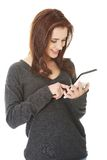 Mujer sonriente que usa una tablilla Imagenes de archivo