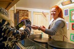 Mujer sonriente que vende la comida en el mercado de la Navidad de Vilna Fotos de archivo