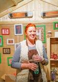 Mujer sonriente que vende la comida en el mercado de la Navidad de Vilna Fotografía de archivo libre de regalías