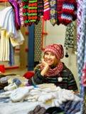 Mujer sonriente que vende la ropa caliente en el mercado de la Navidad de Riga Imagen de archivo libre de regalías