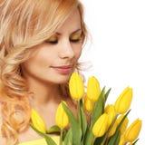 Mujer sonriente rubia con los tulipanes amarillos, aislados Foto de archivo libre de regalías