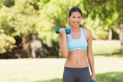 Mujer sonriente sana que ejercita con pesas de gimnasia en parque Fotos de archivo libres de regalías