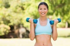 Mujer sonriente sana que ejercita con pesas de gimnasia en parque Fotografía de archivo libre de regalías
