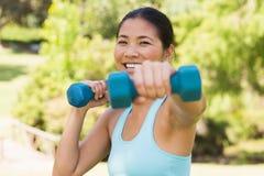 Mujer sonriente sana que ejercita con pesas de gimnasia en parque Foto de archivo libre de regalías