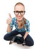 Mujer sonriente sitiing en piso con PC de la tableta Foto de archivo
