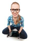 Mujer sonriente sitiing en piso con PC de la tableta Imagenes de archivo