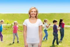 Mujer sonriente sobre el grupo de niños al aire libre Foto de archivo libre de regalías