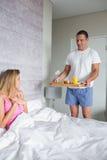 Mujer sonriente sorprendida por el socio que trae el desayuno en cama Imagenes de archivo