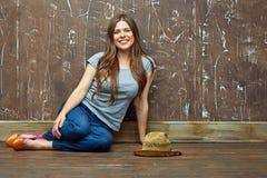 Mujer sonriente vestida casual que se sienta en un piso Fotos de archivo libres de regalías
