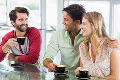 Mujer sonriente y dos hombres que comen la taza de café Imagenes de archivo