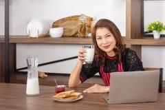 Mujer sonriente y sostener un vidrio de leche imagen de archivo