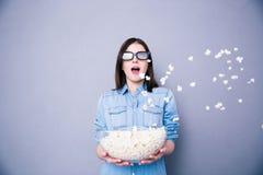 Mujer sorprendente en el cine que se coloca con el cuenco de palomitas Imagen de archivo libre de regalías