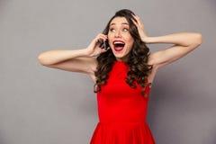 Mujer sorprendente feliz en vestido rojo que habla en el teléfono Fotos de archivo libres de regalías
